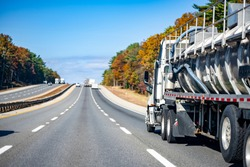 Day cab white big rig semi truck transporting dangerous cargo in red armored tank semi trailer for for the transportation of chemical and flammable substances running on the road in New England
