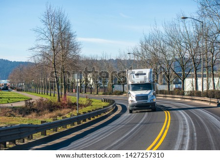 Day cab white classic popular powerful industrial grade big rig semi truck transporting commercial cargo on flat bed semi trailer running on the turning road in sunny day #1427257310