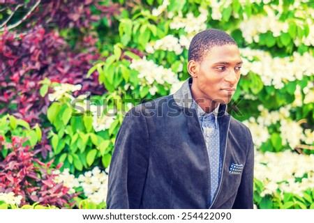 Day Dream. A young black college student standing outside by green, purple, white plants, looking down, thinking, making funny face, smiling. Concept of teenager self esteem. Instagram filtered look.
