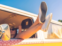 Day dreaming in car. Close-up of young woman holding legs out of the window while sitting inside of minivan