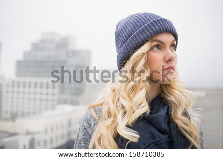 Day dreaming pretty blonde posing outdoors on urban background