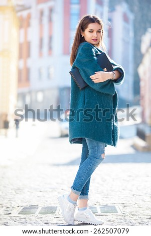 Day dreaming pretty brunette posing outdoors on urban background