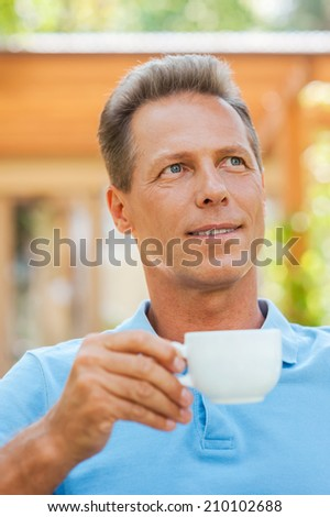 Day dreaming with cup of coffee. Cheerful mature man drinking coffee and smiling while sitting outdoors with house in the background