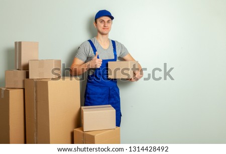 Day moving. Delivery of goods from shopping in the online store. The loader or courier smiles and shows big thumbs up and carries cardboard boxes against the gray wall.