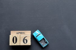 Day 6 of April month, Wooden calendar with date and toy car.Empty space for text.