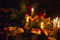 Day of the dead at night in the cemetery of Janitzio, Michoacan, Mexico. Traditional decoration with cempasuchil flowers and candlelight