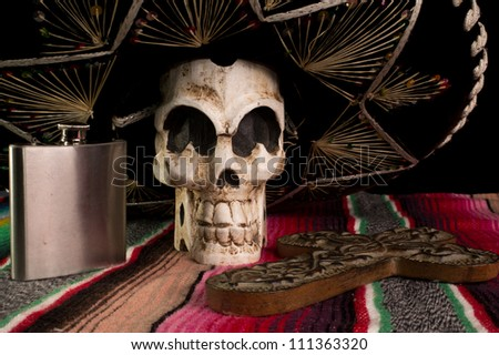 Day of The Dead (Dia de los Muertos) skull with with decorative cross, tequila flask on a traditional mexican blanket.