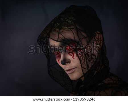 Stock Photo Day of the dead. Halloween. Makeup for Halloween. Portrait of a girl with bleeding eyes.