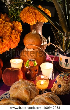 Day of the dead offering altar (Dia de Muertos) Celebration with bread ¨Pan de Muerto¨ chocolate and amaranto skulls and flowery in background.