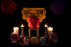 Day of the Dead offering from central Mexico with papel picado, veladoras, photography, flowers and bread of the dead