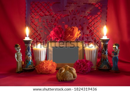 Photo of  Day of the Dead offering from central Mexico with papel picado, veladoras, photography, flowers and bread of the dead