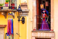 Day of the death. Traditional Mexican Catrina at the window of the old historic building, Guanajuato, Mexico. An elegantly-dressed skeleton figure used as a symbol of the Day of the Dead