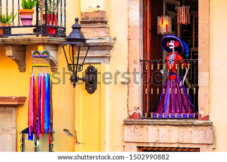 Day of the death. Traditional Mexican Catrina at the window of the old historic building, Guanajuato, Mexico. An elegantly-dressed skeleton figure used as a symbol of the Day of the Dead Foto stock ©