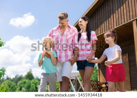 Day outside city. Happy good-looking active family spending day outside the city all together