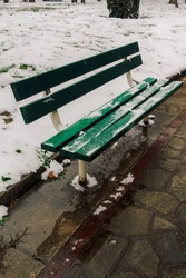 Day view of an empty wooden green bench at a park area partly covered with snow.