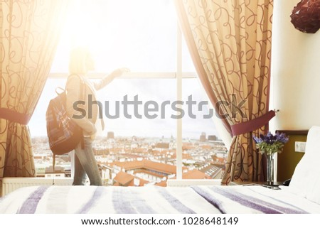 Daybreak at the hotel room. Young female traveller watching cityscape, standing near big window. Happy girl with backpack ready to explore new city. Travelling and accomodation concept, copy space