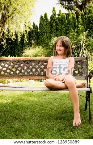 Daydreaming child portrait - little girl sitting on bench outdoor in backyard
