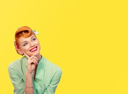 Daydreaming. Closeup red head young woman pretty smiling pinup girl green button shirt  dreaming about love career money looking up retro vintage 50's hairstyle. Body language Positive emotion feeling