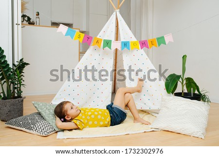 Photo of  Daydreaming happy little girl lying on a blanket in front of a hut, made with sticks and bedsheets. Her mind wanders far away in a magical land.