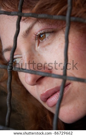 daydreaming of a young woman behind the fence