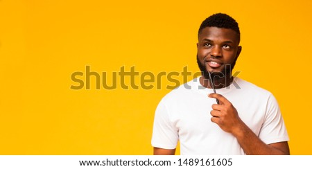 Daydreaming. Pensive Man Touching His Chin While Thinking On Yellow Studio Background. Free Space