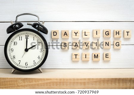 Daylight Saving Time - Black Vintage Alarm Clock and Wooden Letters on White Painted Planks Background #720937969