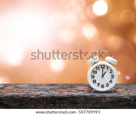 Daylight saving time end concept with alarm clock on orange autumn blur background