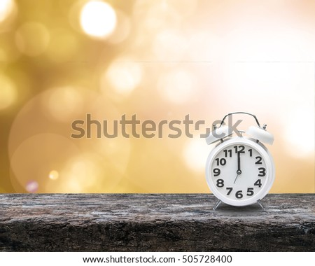 Daylight saving time end concept with alarm clock on yellow gold autumn blur background