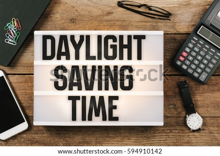 Daylight Saving Time in vintage style light box on office desktop, high angle birds eye view #594910142
