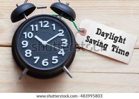 Daylight Saving Time words written on tag label with clock on wood background,Conceptual #483995803