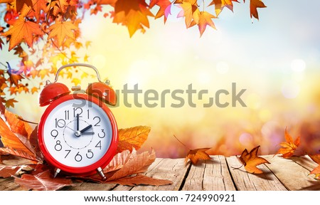 Daylight Savings Time Concept - Clock And Leaves On Wooden Table #724990921