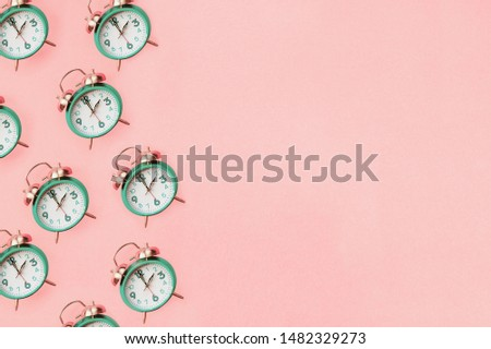 Daylight savings time concept. Set your clocks back with this flat lay retro beautiful alarm clocks set to 2 am over pink background. Pattern. Top view with copy space.
