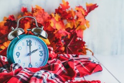 Daylight savings time concept. Set your clocks back with this retro beautiful alarm clocks set to 2 am over rustic white background with red plaid scarf and autumn leaves. Free space for text.