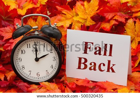 Daylight Savings Time Ends, Some fall leaves, black and white alarm clock and a blank greeting card with copy-space #500320435