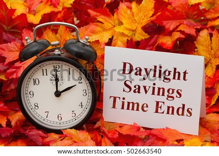 Daylight Savings Time Ends, Some fall leaves, black and white alarm clock and a blank greeting card with copy-space #502663540