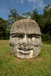 Daytime ground level view of an ancient carved basalt Olmec Colossal head.