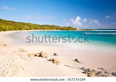 Daytime long exposure of the beautiful Half Moon Bay in Antigua.
