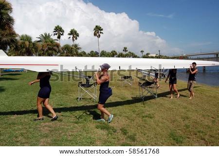 "DAYTONA BEACH, FL - JULY 24:  Rowers shoulder the racing shell during the  ""Halifax Rowing Association's Summer Regatta 2010"" on July 24, 2010 in Daytona Beach, Florida."