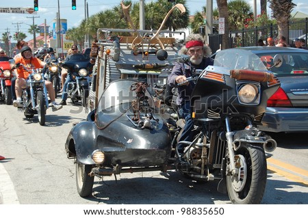 "DAYTONA BEACH, FL - MARCH 17:  A customized motorcycle towing a trailer cruises Main Street on St. Patrick's Day during ""Bike Week 2012"" in Daytona Beach, Florida."