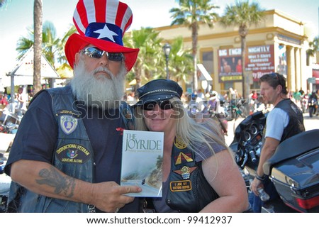 "DAYTONA BEACH, FL - MARCH 17:  Pastors Montana and Joy Mormur promote her book ""The JoyRide"" and their Church on Wheels ministry on Main Street during ""Bike Week 2012"" in Daytona Beach, Florida."