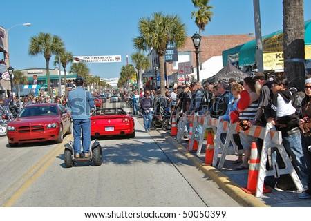 "DAYTONA BEACH, FL - MARCH 6:  Spectators watch all types of vehicles cruise down Main Street amid the sea of bikers in town for ""Bike Week 2010"" in Daytona Beach, Florida."