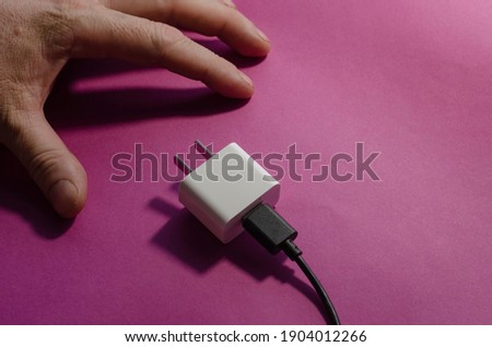 DC adapter with USB data cable and man's hand on a pink background. Smartphone charger adapted for the USA. Selective focus. Photo stock ©