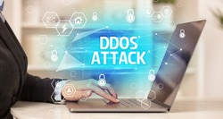 DDOS ATTACK inscription on laptop, internet security and data protection concept, blockchain and cybersecurity