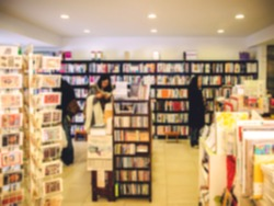 De focused/Blur image of a bookstore with customers reading and looking for books. Toned image. Warm tone. Bookstore background.