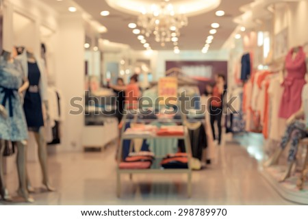 De focused/Blur image of a dress store with customers and dressed mannequins.