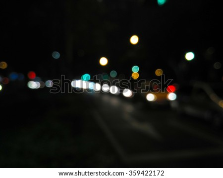 De focused/blur image of city at night. A man crossing the road. De focused, blurred urban abstract traffic background.