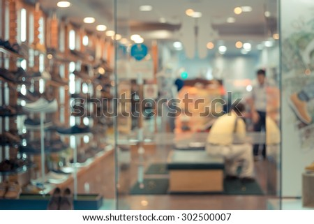 De focused/Blurred image of a shoe store with a staff and a customer in it.