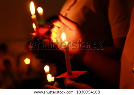 Photo of  De focused Candlelight with people. Bokeh of light candle,Crowds gather to do candlelight activities. Closeup of people holding candle vigil in darkness expressing and seeking hope.