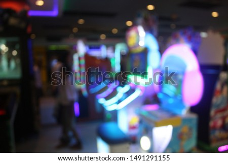 De focused image of children and teenagers that enjoy playing the coin operate game cabinet in the shopping mall. Blurry and bokeh light effect in the city. Selective focus.