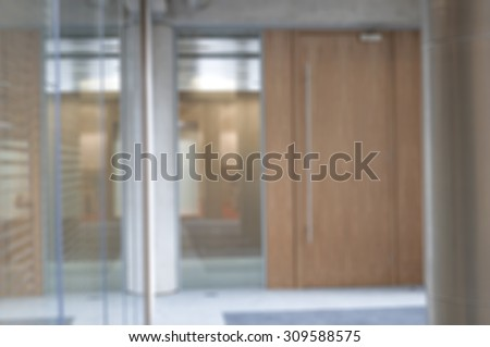 De-focused office environment with glass partitions and wood doors